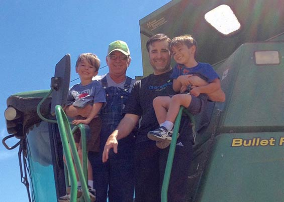 Jeremy Fouts working on a combine tractor with his father and two boys on their farm in Spiro, OK.